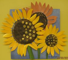 Recycled laundry detergent bottles, paper mache, and found objects were used to make this sunflower relief. Titled: Ready For Harvest.