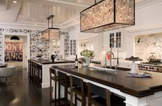kitchen- love the double islands, long linear hanging lights above, tray ceiling details and graphic wallpaper