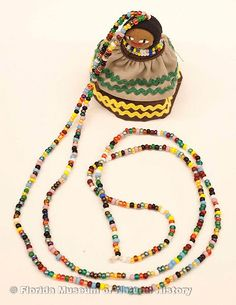 """Ethnographic Collection :: Florida Museum of Natural History. Doll, female, necklace, Seminole, cotton cloth, glass beads, palm fiber, ca. 2000, doll is 2.5"""" high (2006-20-8)."""