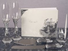 Silver Fairytale Castle Wedding Collection. An enchanting silver castle collection which contains set a guest book, pen set, cake and knife server set, and a set of toasting glasses. Silver resin with silver sparking epoxy accents.