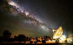 The Milky Way appears to line up with the giant 64-m dish of the radio telescope at Parkes Observatory in Australia. As can be seen from the artificial lights around the telescope, light pollution is not a problem for radio astronomers. Radio and microwave interference is a big issue however, as it masks the faint natural emissions from distant objects in space. For this reason many radio observatories ban mobile phone use on their premises.