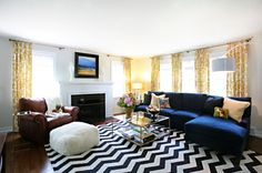 blue velvet couch with yellow curtains and black/white rug