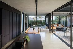 The pavilion at the rear of the villa is soaked in sunlight from both the north and the east. The bright light is countered with bold interjections of black steel and concrete. Outdoor Seating Areas, Outdoor Spaces, Villa Game, Aluminium Joinery, Sliding Screen Doors, Gone Rogue, Modern Backyard, Home Reno, Glass House