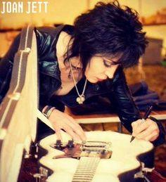 Joan Jett signing a guitar