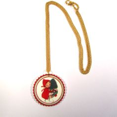 Vintage style circular scalloped edge print pendant, with pretty image of a smiling little girl dressed as Little Red Riding Hood carrying a Christmas tree. Precious! Fashioned from 3mm laser-cut acrylic. On a 46cm gold plated curb chain.  Pendant measures approximately 37mm x 37mm. Nickel and lead free. Oh but she's gorgeous. I definitely do not want wolf to eat her.