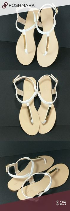 Calvin Klein white and gold T-strap sandals Size 8.5   Brand new Calvin Klein faux leather t-strap sandals with gold accents. no tags.  Like new. I've tried them on, but never wore them out.   Almost perfect condition. The final 2 pictures show tiny indentions that were made on the back of both shoes from a clippy hanger I used to hang them in my closet. I'm throwing away this evil hanger!!  😅  Happy Poshing! Calvin Klein Shoes Sandals