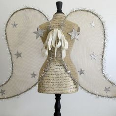 Love this Christmas decor—dress form with gold net angel wings❣