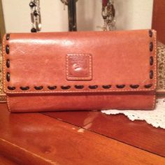 """Dooney & Bourke Florentine Wallet/Clutch  Dooney & Bourke Whiskey Brown Florentine Continental Clutch/Wallet and checkbook. The leather is in great condition on the outside shows a little wear and in the inside shows a little wear on the leather also no tears rips or discoloring. Size 7.5 long X 4"""" X 1"""". Comes from a non-smoking home pet free. I ship within 24 hours Monday through Friday. If you have any questions please ask! ☝️ Dooney & Bourke Bags Wallets"""