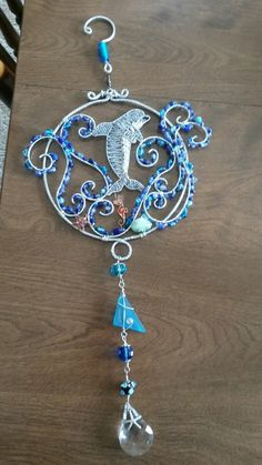 Wire wrapped beaded sun catcher with dolphin seahorse starfish shells.