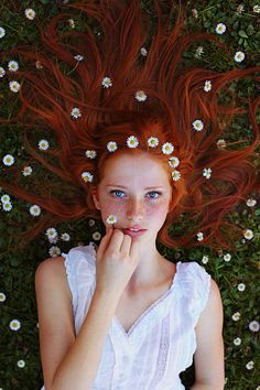 Beautiful teenage girl lying in a field of daisies