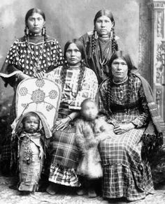 "Shoshone Indian Women and Child, and Indian Baby in a Beaded Buckskin-covered Cradleboard. Woman on the left top row wears a Traditional ""Elk Teeth"" Clothe Dress. The Traditional Floral Beadwork design on the Cradleboard resembles Nez Perce & Columbia River Tribal Contour Beadwork Patterns. Thnx."