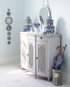"Blue Wedgwood Tins - Tin containers have been manufactured in a very cool color of Wedgwood jasperware. For display on a neoclassic sideboard, we've chosen grays, blues, and greens. Symmetrically arranged with eighteenth-century formality, stacks of the circular ""Wedgwood"" tins can be used for storage. On the wall, a row of lids is displayed like a collection of antique plates or prints."
