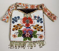 "Plains Beaded Bandolier Bag - 19th/20th century, having a florally worked front, green velvet backing and a loom beaded strap. Bag excluding fringe: 11 1/2"" long, 11"" wide, strap: 20"" long, 1 3/4"" wide."