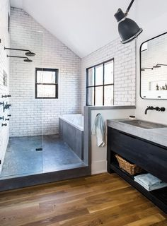 In the master bathroom, a modern farmhouse aesthetic took an industrial bent with brick walls, a concrete shower floor, and metal windows—the latter providing a view of horses. dusche Room Envy: At Serenbe, a master bath with a modern farmhouse aesthetic Modern Farmhouse Style, Farmhouse Style Decorating, Rustic Farmhouse, Modern Rustic, Farmhouse Ideas, Farmhouse Design, Farmhouse Addition, Farmhouse Contemporary, Farmhouse Remodel