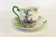 This beautiful teacup and saucer set was made by Royal Albert in England. The pattern is called Greenwood Tree. Both pieces are decorated with trees and colorful flowers on a white background. The rims of both pieces are green as well as the handle of the teacup. They are marked, Royal Albert, Bone China, England, Greenwood Tree, Reg. No. 774783. This back stamp dates the set to the 1940s.  Condition: This set is in very good, vintage condition. There are some spots of paint that are under…