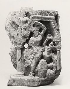 Fragment of a panel showing a musician and dancer, perhaps from a scene of the Bodhisattva in his palace. The dancer wears heavy anklets, multiple bracelets, a collar and earrings, a tunic with a paridhāna round it and a scarf tucked into its girdle; the headdress may be a wreath with a loop of hair. She raises one leg and arm, and her other arm crosses the body to the thigh. The Figures (group of). Dancing woman and drummer. Made of stone (schist).