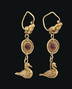 A PAIR OF GRAECO-ROMAN GOLD AND GARNET EARRINGS   CIRCA 1ST CENTURY B.C.-3RD CENTURY A.D.   Each composed of large hoop with a goat head terminal, with long twisted wire horns, a disc suspended below centred by a cabochon garnet surrounded by bands of twisted, plaited and plain wire, a pendant bird below, its wings, tail feathers, feet and eyes all with twisted wire decoration