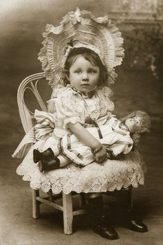 Well dressed Victorian little girl with large porcelain head doll. I love her HUGE! hat and lacey dress.