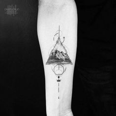Graphic mountain tattoo on the right inner forearm.