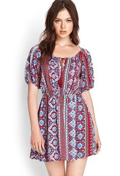 This peasant dress features a vibrant folk print and tasseled round neckline. Complete with croch...