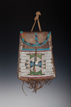 """Sioux Beaded Dispatch Bag. Constructed from commercially tanned hide with seed beads, sinew and a cowrie shell. 10 1/2"""" long including the fringe, 5"""" wide at the top, tapering to 7"""" wide at the base. Circa 1870. Brian Lebel's High Noon Auction, Jan. 2015."""