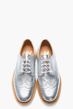 METALLIC SILVER LEATHER COUNTRY BROGUES 31423M049007  Low top leather wingtip brogues in metallic silver. Round toe. White lace up closure with white eyelets. Signature decorative perforation and serrated edges throughout. Tan welt with white stitching. White rubber foxing. Grey stitching. Leather upper, rubber sole. Made in United Kingdom.