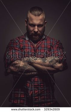 Man with beard and tattoo isolated on grey background. Crossed arms. - stock photo