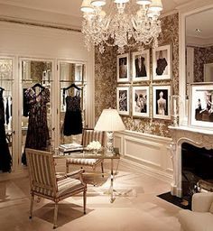 this feminine, chic dressing room has a beautiful crystal chandelier, mirrored doors, gallery wall, table & chairs & a FIREPLACE!!!