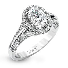 This lovely 18k white gold engagement ring design is created for an elegant oval center stone and features .77 ctw of white diamonds accented by a small touch of .03 ctw of yellow diamonds.