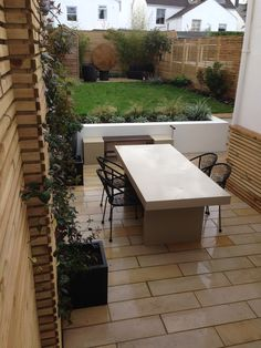 Rectilinear design for a garden in Brighton, with sawn mint sandstone paving, white rendered walls and batten screening. The garden includes evergreen tropical style planting and a corten steel circular sheet as a focal point at the rear of the garden.