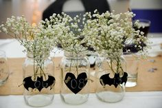 I love these. Maybe I'd use black stenciled images on burlap around the jars, with more elegant flowers inside