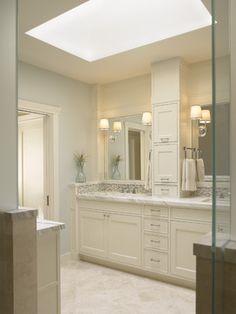 Serene bath with storage tower between vanities