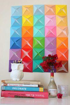 Esse painel de origamis é lindo, não é?    Para criar esse efeito, basta pegar papéis de origami e unir as pontas do quadrado no centro. Depois, é só colar lado a lado em uma cartolina e colar na parede com fita adesiva. Se gostou, compartilhe a ideia!