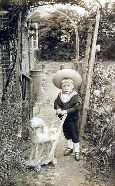 Found image. An Edwardian lad in a straw hat and a sailor suit pushing a wooden horse.