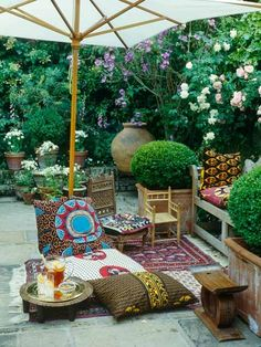 Lots of foliage and container gardens; chaise with colorful pillows; wicker love seat or 2 wicker chairs and small table