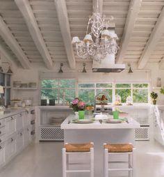 Super wonderful white kitchen, large beams, slanted roof, center island, chandelier with white shades via:DESDE MY VENTANA: Un cocina Blanca / A White Kitchen