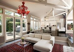Gorgeous Murano red glass chandelier enlivens the bright and airy living room