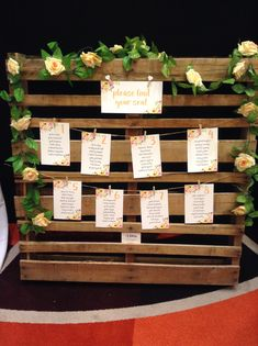 Our brand new Secret Garden rustic pallet seating chart featuring peach and apricot florals, peach pink rose garland and cute little wooden pegs