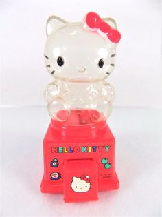 #1990s #90s #vintage 1976 1992 100% genuine authentic #Sanrio Hello Kitty character print green, red, yellow, black, white and blue #candy #gum #gumball #bubblegum machine #dispenser with removable #figurine top, lever handle, door with flap closure, plastic base, clear transparent acrylic top and a fun multi-colored design on front, excellent used condition…