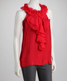 This top boasts contemporary style with an air of mystery. A cloth-petaled neck supports an eye-catching fall of frills.