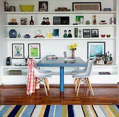 O escritório Suíte Arquitetos apostou em uma cor forte para a mesa de múltiplo uso. O azul a fez ganhar destaque entre as prateleiras brancas da estante. O móvel serve o jantar, funciona como escritório e reúne amigos no carteado
