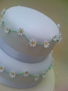 I like the daisy chains too - but would rather them around the base of the cake