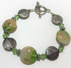 Vintage Boho art glass bead bracelet Beautful swirled lampwork disk glass beads in transparent green, off white and swirls of color alternate with textured antiqued silver tone disk beads Glass beads are 3/4 inches in diameter, silver tone ones are 5/8 inches 8 1/2 total length, will fit a medium to large wrist I believe this is hand crafted Toggle clasp Unsigned Good vintage condition, shows no wear 61919