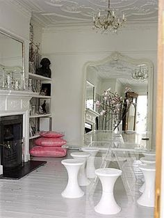 Introducing a lucite piece into a traditional setting adds punch to an outdated interior. Then add a vintage piece to that mix and you are on your way to Bohemian Chic. Below, a modern lucite table, 60s stools, and a traditional floor mirror with a painted white frame in a lush old-world setting.