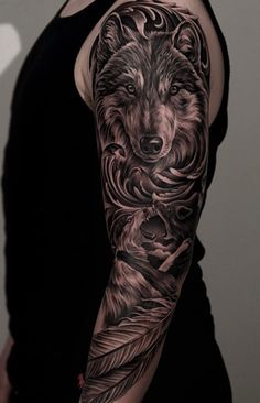 A majestic looking sleeve tattoo. The tattoo shows a face of a wolf who is seemingly ready for an attack and has sheer determination n the eyes. Below it are two more wolves engaging in a fierce battle for superiority.