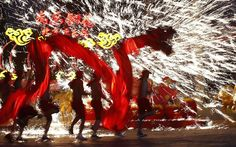 Dancers perform a fire dragon dance in the shower of molten iron spewing firework-like sparks during a folk art performance in Beijing as part of Chinese New Year celebrations.