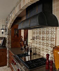 Custom cabinets from Extraordinary Works shows storage area behind stone column and iron details in custom cook top hood. Virginia Tile patterned backsplash, drapery fabric from Duralee. Valerie Young Interiors Valerie L. Young - Lake Orion, MI
