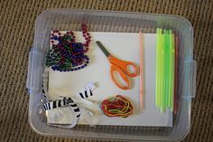 Cutting box.    Mardi gras beads, ribbon, string, straws, and scissors.