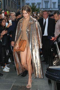 Gigi Hadid hits Milan in a nude bodysuit and metallic trench coat during fashion week.