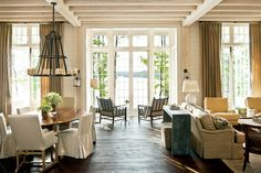 """Connection to the Outdoors - 24 Lake House Decorating Ideas - Southernliving. """"I always design floor plans to pull visitors toward the daylight,"""" says Bill. Here, the elevated entry and foyer give guests a straight view to the lake upon entering the front door. There are also three outdoor living spaces: a rear terrace, a screened side porch, and an open-air porch.  See more of the Bill Ingram Lake House"""